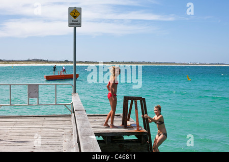 Young girls swimming at Middleton Beach jetty. Middleton Beach, Albany, Western Australia, Australia - Stock Photo