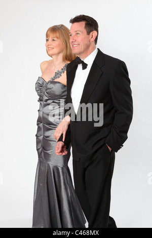 Couple wearing smart evening dress and suit with bow tie. - Stock Photo