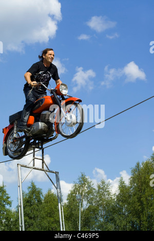 motorcycle driver balancing on rope - Stock Photo