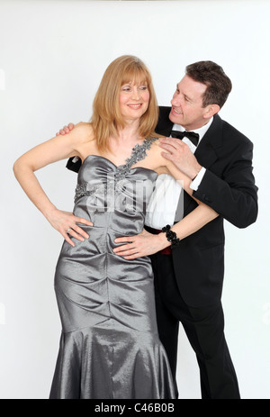 Woman wearing long formal dress hands on hips, man hands on her shoulders, both looking at each other with cheeky - Stock Photo