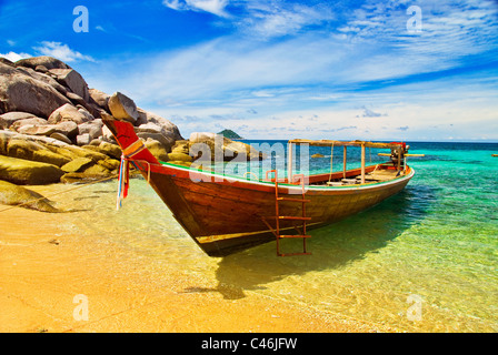 Thai Longtail Boat Anchored in a Turqouise Bay - Stock Photo