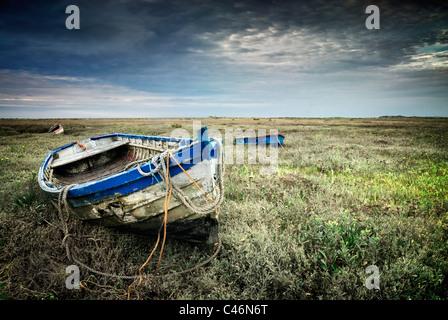Old fishing boat on the saltmarshes on the coastline of North Norfolk, at Burnham Deepdale, Norfolk, England,UK - Stock Photo