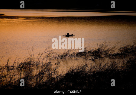 Photograph of a fishing boat in the Sea of Galilee at sunset - Stock Photo