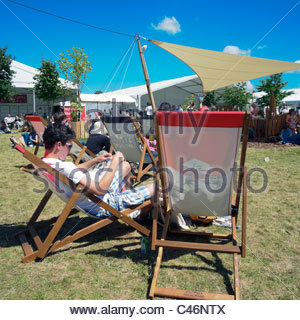 Hay on Wye, Wales, UK. Hay festival man reading a book sitting in a deckchair. - Stock Photo