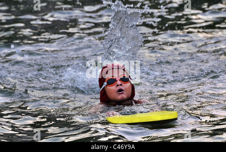 Young Bengali, Asian Boy is being trained in swimming. Practicing with yellow float board, wearing red cap and orange - Stock Photo