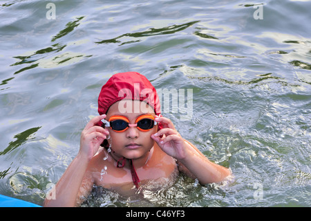 Young Bengali, Asian Boy is being trained in swimming. Practicing, wearing red cap and orange goggles - Stock Photo