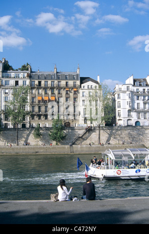 Couple sits on banks of the seine river in Paris St. Germaine area in late spring - Stock Photo