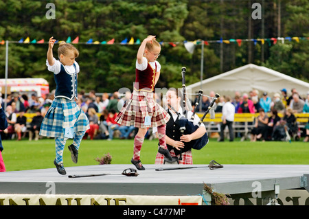 Lonach Highland Games at Strathdon, Grampian, Scotland. Piper plays for young girls performing traditional sword - Stock Photo