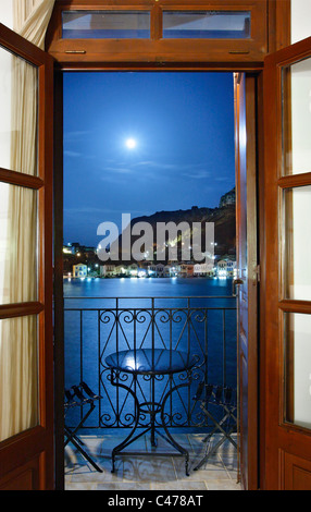 Night  view  of the picturesque village of Kastellorizo (or 'Meghisti') island, through the door of a hotel room, - Stock Photo