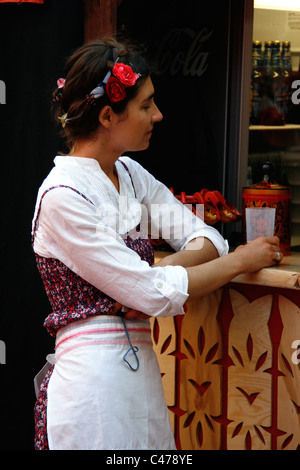 A young Russian woman with floral wreath in the hair is drinking at a bar / food stall during a festival in the - Stock Photo