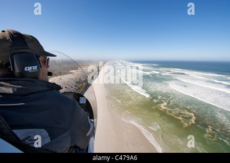 Aerial view over the shoulder of a gryocopter pilot flying along the beach near Yzerfontein north of Cape Town in - Stock Photo