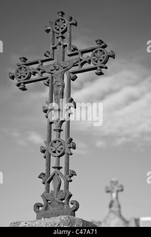A rusty decorative cross with Jesus at it's centre against the sky with a stone cross in the background - Stock Photo