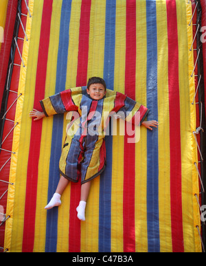 Boy playing on velcro sticky wall in colorful suit - Stock Photo
