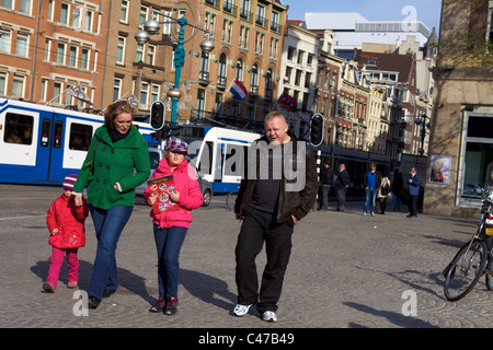 Tourists at Dam Square in Amsterdam, Holland, the Netherlands - Stock Photo