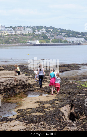 With beautiful beaches at our doorstep a single mum with large family at the seaside at low tide iTorquay,Devon,family - Stock Photo