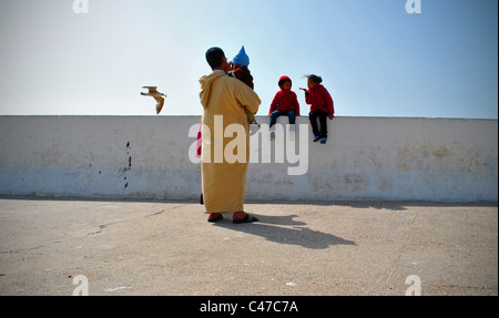 Moroccan family by the sea wall in Essaouira, Morocco - Stock Photo