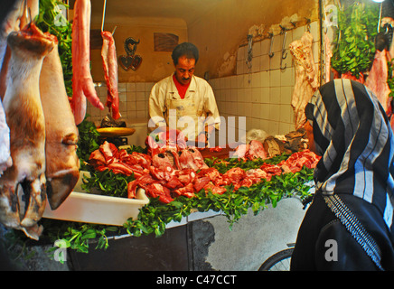 Woman buying from a butcher's in Marrakesh, Morocco - Stock Photo