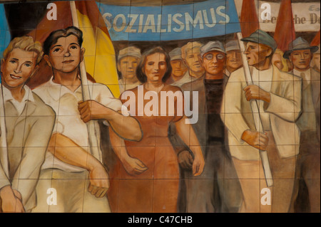 Socialist realist mural on a building in Berlin, Germany depicting young male and female musicians leading a parade. - Stock Photo