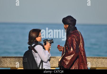 Woman taking a photo of a Tunisian man in Sousse, Tunisia - Stock Photo
