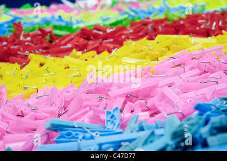 Different colored plastic clothes pins on a counter in an open marketplace - Stock Photo