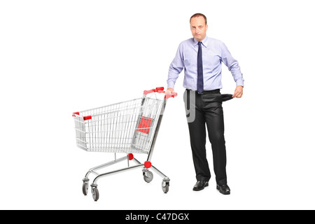 Bankrupt businessman turns out his empty pocket and an empty shopping cart - Stock Photo