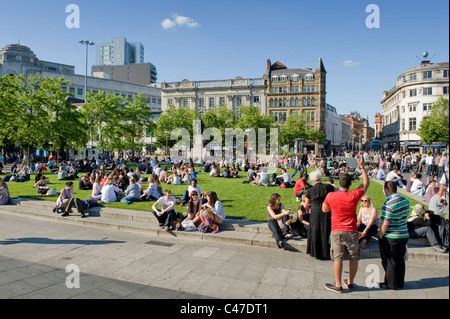 People congregate in the crowded Piccadilly Gardens, Manchester on a hot, sunny day. - Stock Photo