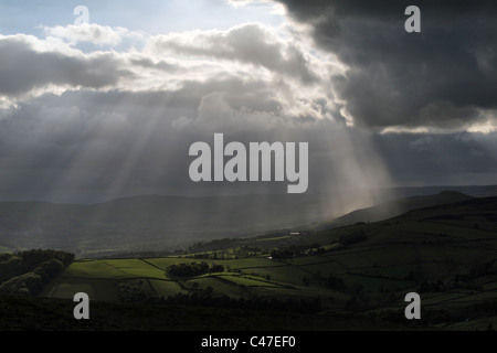 beautiful sunburst sun rays bursting through clouds shines light over the countryside in the Peak District Derbyshire - Stock Photo
