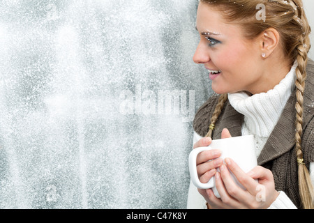 Amazed female with cup in hands looking through frosty window - Stock Photo
