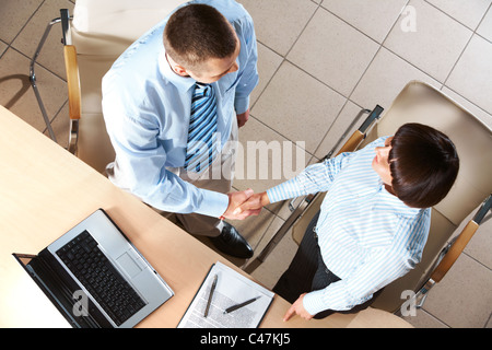 Photo of two business partners congratulating each other on signing promising contract