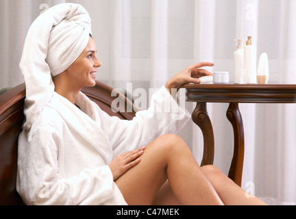 Portrait of pretty female taking care of her skin after bath - Stock Photo