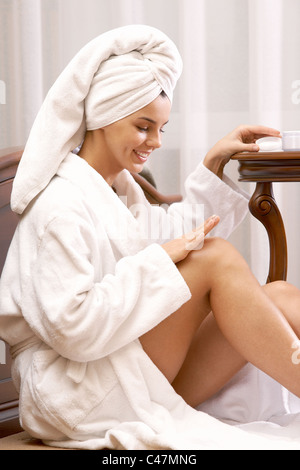 Portrait of pretty female taking care of her hands after bath - Stock Photo