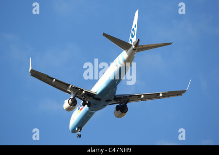 Jet Aeroplane flying over head coming in to land against a blue sky - Fly be - Stock Photo