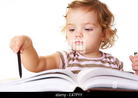 Photo of adorable girl with black highlighter in front of open book - Stock Photo