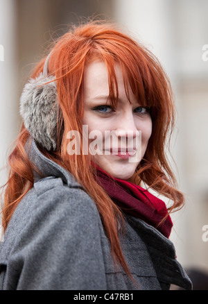 Headshot portrait of a ginger haired teenager wearing earmuffs in winter, London, England, UK, GB. - Stock Photo