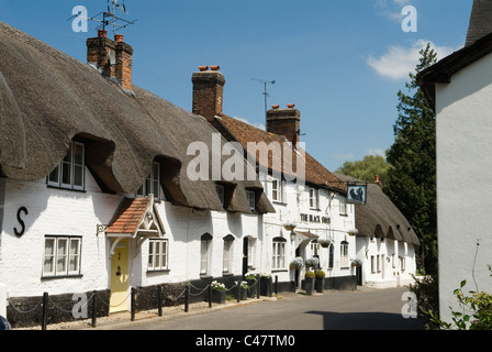 Thatched white cottage Monxton nr Andover Hampshire England. The village pub the Black Swan  HOMER SYKES - Stock Photo