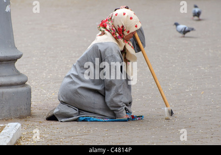 An old woman begging alms in the street - Stock Photo