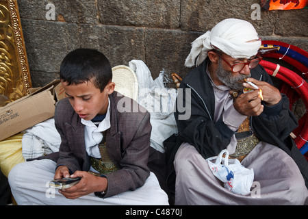 A young boy plays with a mobile phone while the older man lights up his cigarette at the market in the old town - Stock Photo