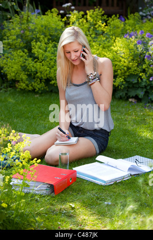 Young girl student chatting and socializing on moblie phone while studying in the garden - Stock Photo