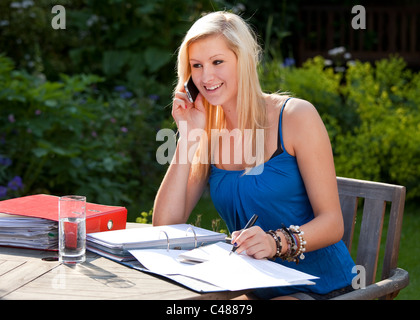 Happy teenage girl student working and chatting on moblie phone in garden - Stock Photo