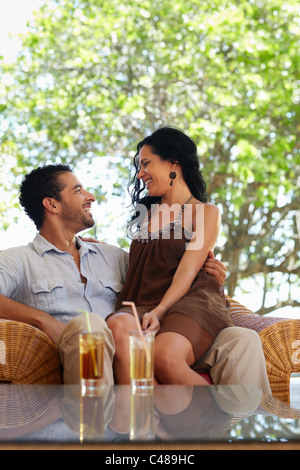 honeymoon: young just married hispanic couple sitting on armchair in hotel bar. Vertical shape, copy space - Stock Photo
