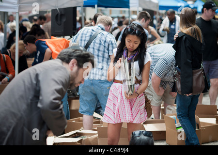 Shoppers search for bargains amidst the chaos of the Housing Works street fair in the New York neighborhood of Soho - Stock Photo