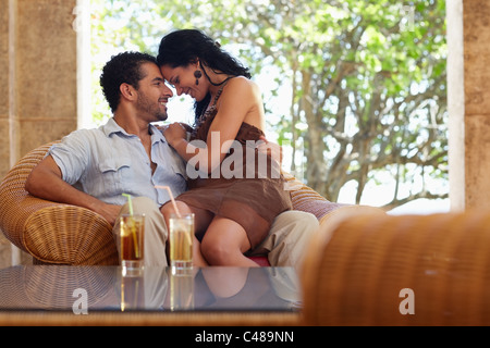 honeymoon: young just married hispanic couple sitting on armchair in hotel bar and hugging. Horizontal shape - Stock Photo