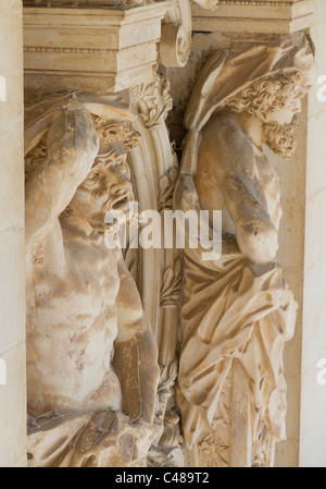 carved stone figures suffer under the load: pillar decoration on university campus in Coimbra, Portugal - Stock Photo