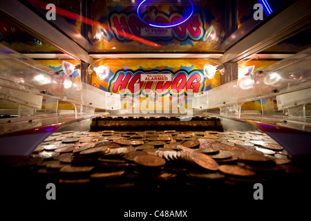 Two pence coins rest piled up and possibly about to fall in a seaside resort amusement arcade machine. - Stock Photo