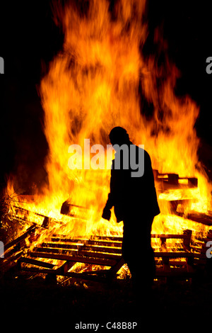 Man silhouetted against a roaring bonfire - Stock Photo