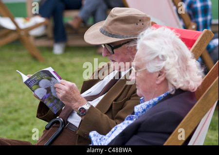 Elderly couple reading festival programme sitting in deckchairs at Hay Festival 2011 - Stock Photo