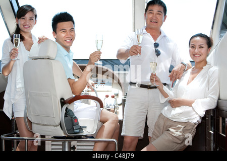 Friends Toasting Champagne on a Yacht - Stock Photo