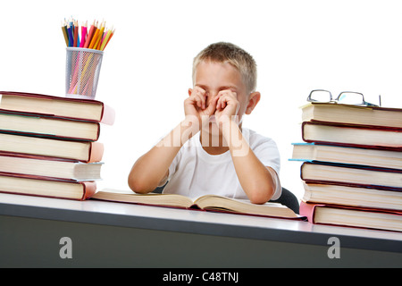 Portrait of sleepy lad rubbing eyes showing his being tired of reading - Stock Photo