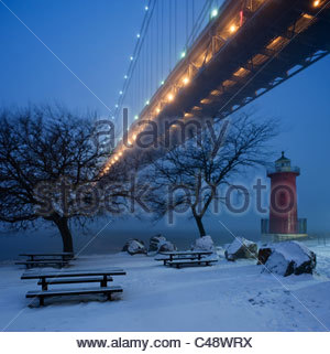 A little red lighthouse sits beneath a large bridge in the snow at dusk. - Stock Photo
