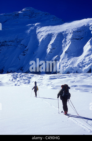 Two men ski touring under sunny skies in the shadow of the north face of Mount Everest. - Stock Photo